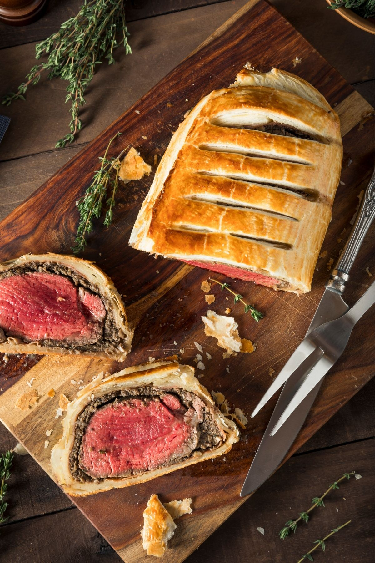 Beef Wellington on a cutting board with thyme. Best substitute for mushrooms in  beef Wellington.