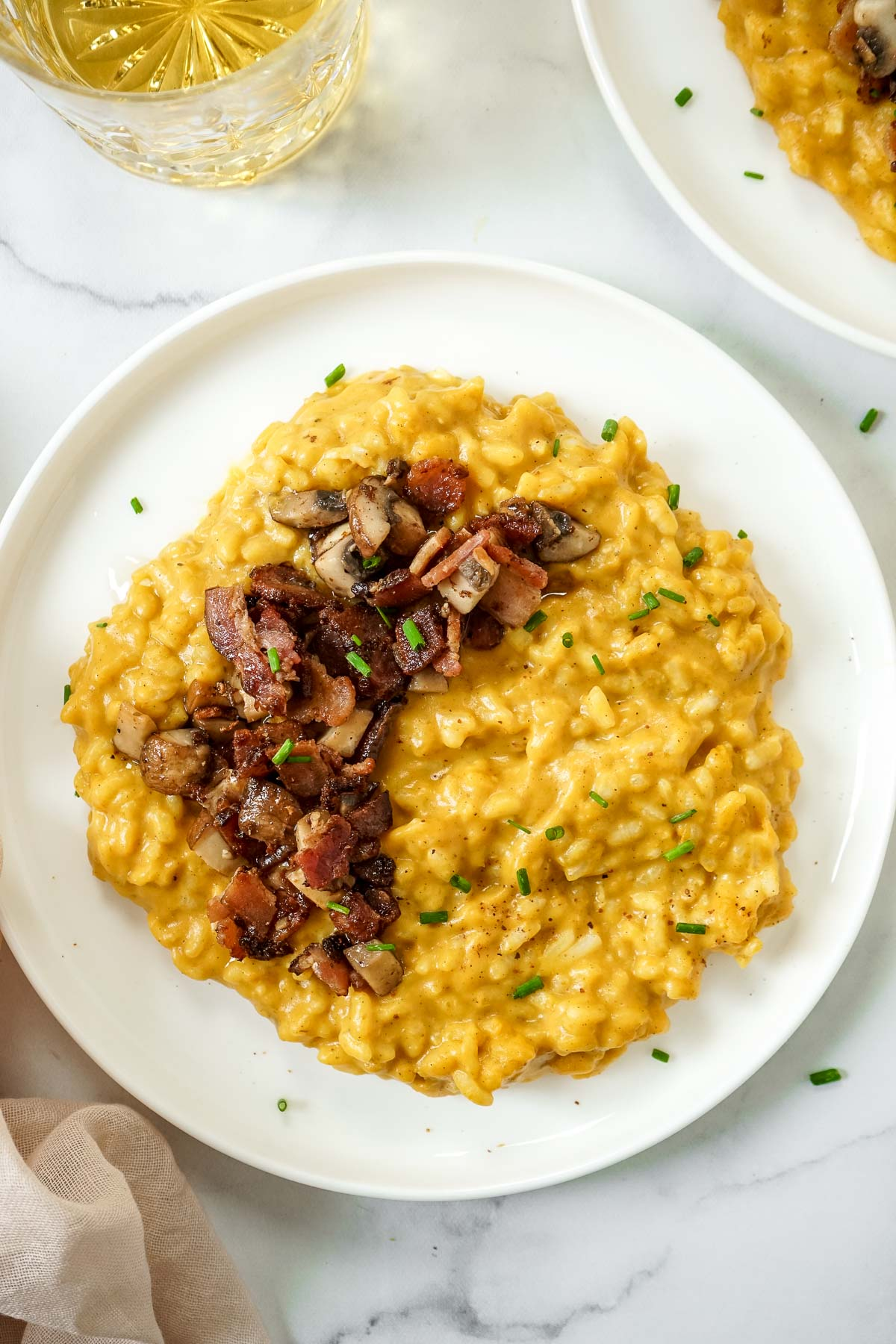 Pumpkin risotto with mushrooms and bacon on a white plate.