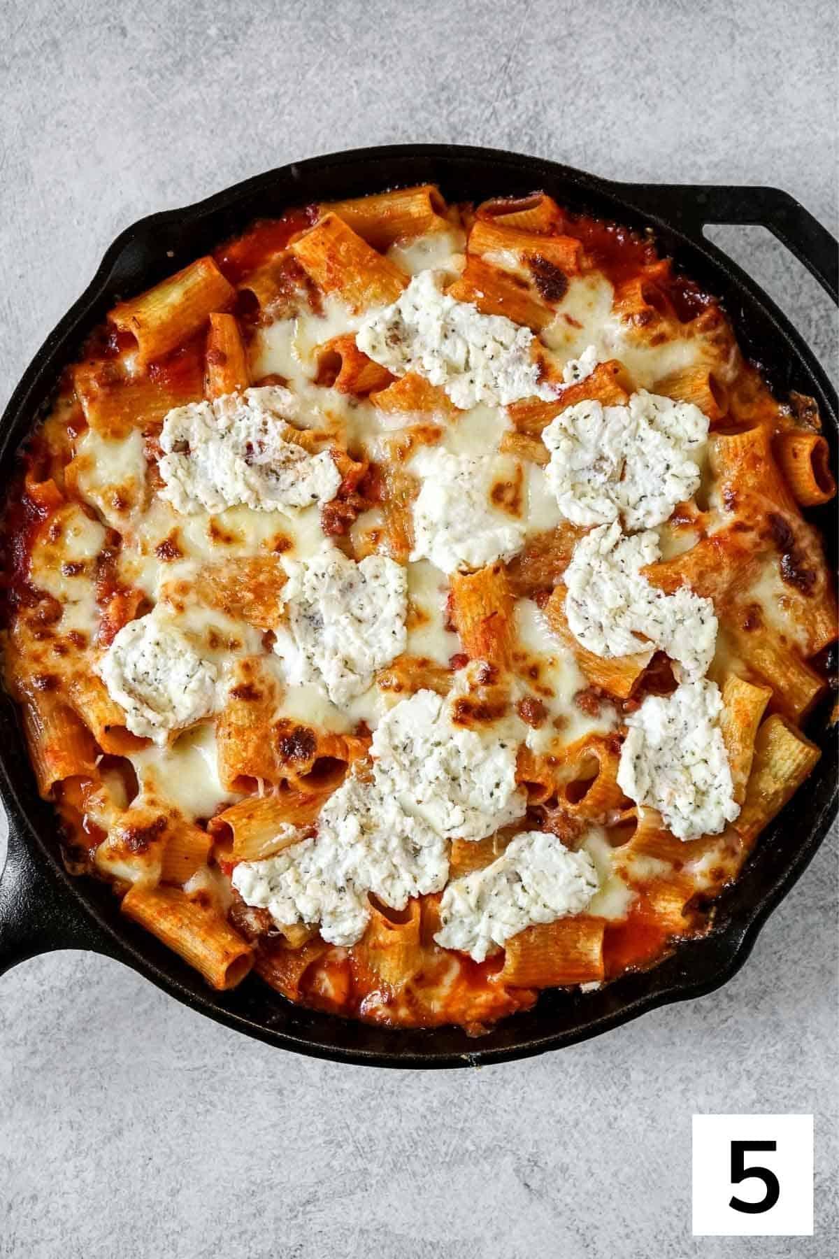 Last step of how to make rigatoni al forno.
