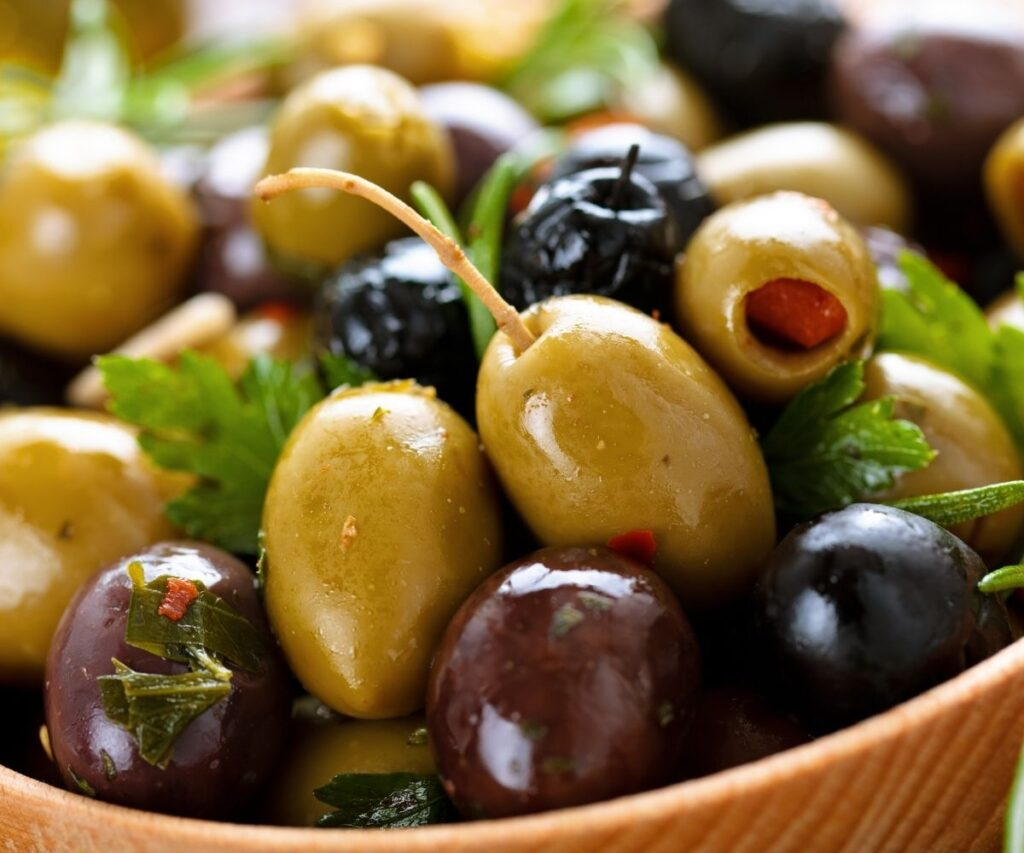 Green and black olives in a wooden bowl.