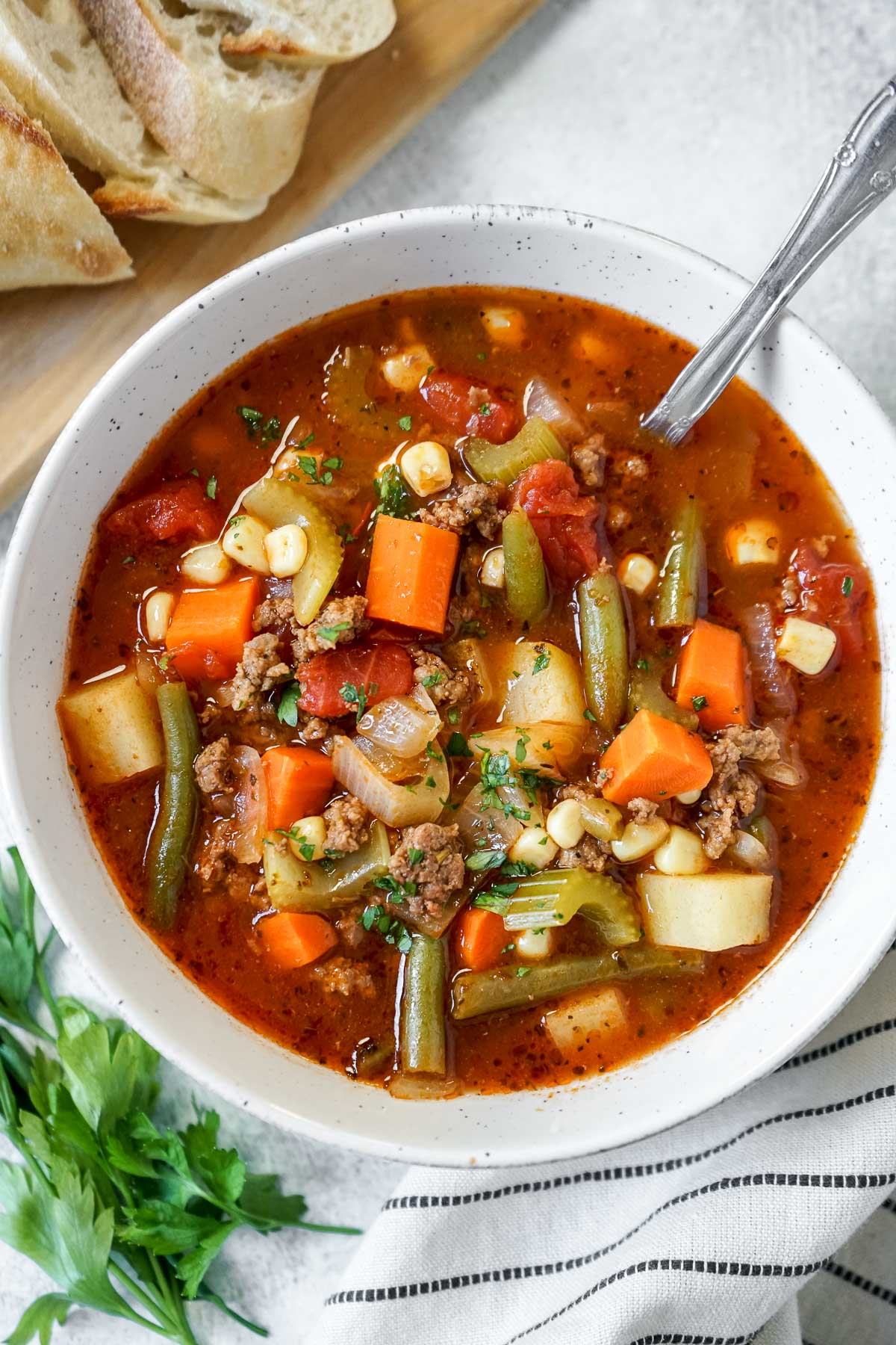Vegetable Beef Soup in a bowl with a spoon and crusty french bread.